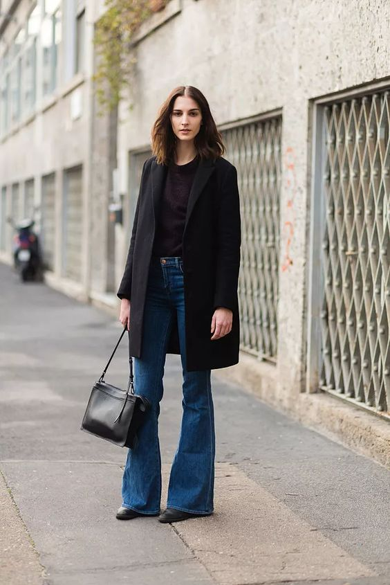 a classy and simple fall look with a black top, blue flare jeans, a black coat and a bag is a stylish solution