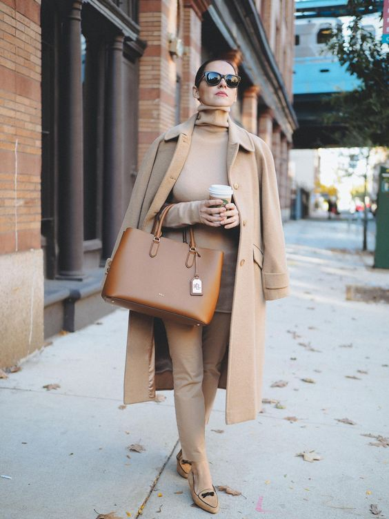 a comfotable outfit in tan, with a turtleneck, trousers, a coat, a brown bag and loafers for a chic fall work look