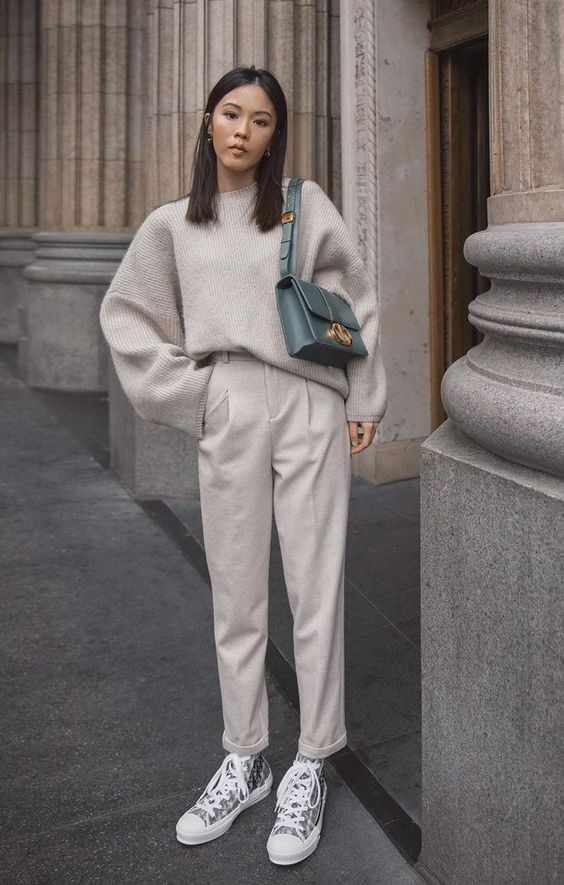 a comfy grey outfit with an oversized sweater, trousers, sneakers and a green bag for a color accent