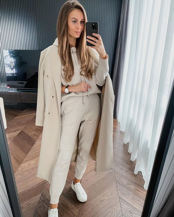 a comfy monochromatic look with a neutral hoodie, sweatpants, white sneakers and a creamy coat is simple and very chic