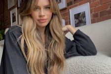 a dark root paired up with long honey blonde waves and logn curtain bangs look very girlish and very beautiful