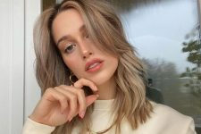 a delicate mushroom blonde shade, medium wavy hair and long curtain banfs for a stylish and relaxed look