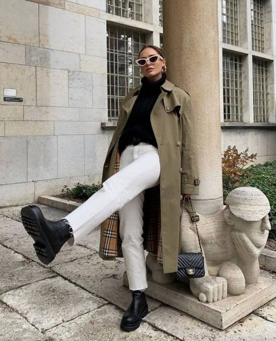 a fall look with a black turtleneck, white jeans, black boots, a green trench and a black bag for the fall