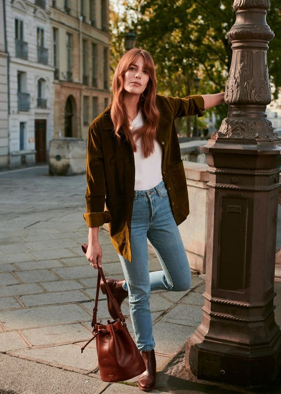 a fall-toned look with a white tee, blue jeans, a mustard-colored velvet blazer, a burgundy bag and booties