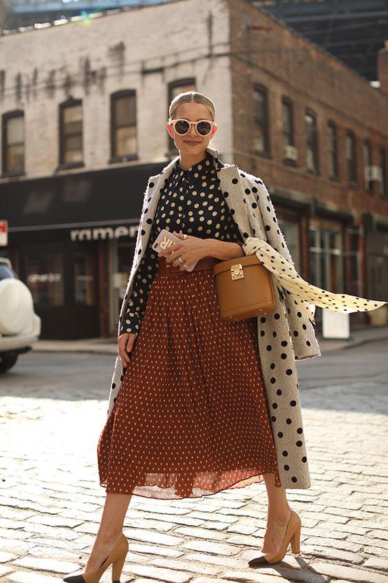a fantastic mix print outfit with a black polka dot blouse, an orange polka dot midi, a white polka dot coat, two tone shoes and a tan bag