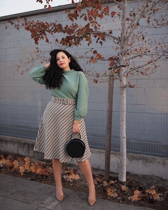 a feminine fall work outfit with a greey sweatshirt, a plaid midi A-line skirt, tan shoes and a black round bag