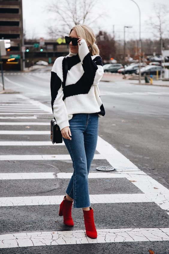 a geometric black and white sweater, blue flare jeans, red booties and a black bag for fall or fall to winter