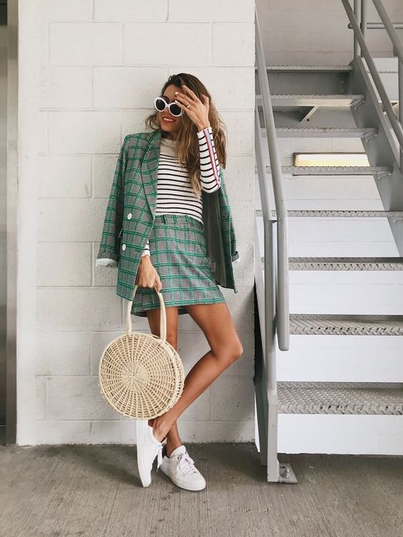 a grey and green plaid suit with a mini skirt, a striped long sleeve top, white sneakers and a woven bag for a summer to fall look