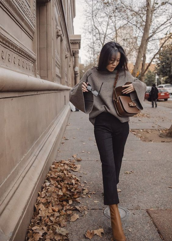 a grey jumper with flare sleeves, black cropped jeans, rust-colored boots and a brrown crossbody bag for a cool and easy look