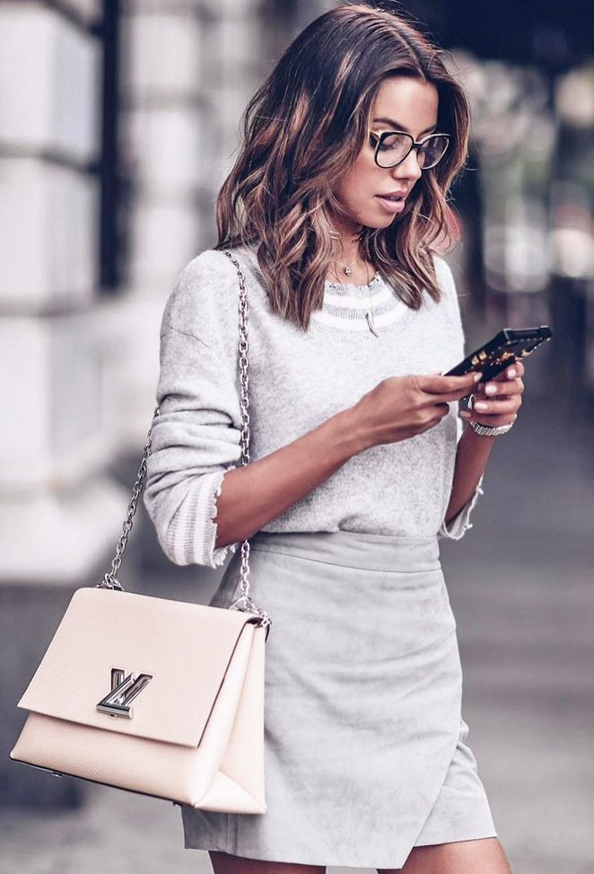 a grey jumper with striped detailing, a grey wrap suede mini and a blush bag plus statement eyeglasses