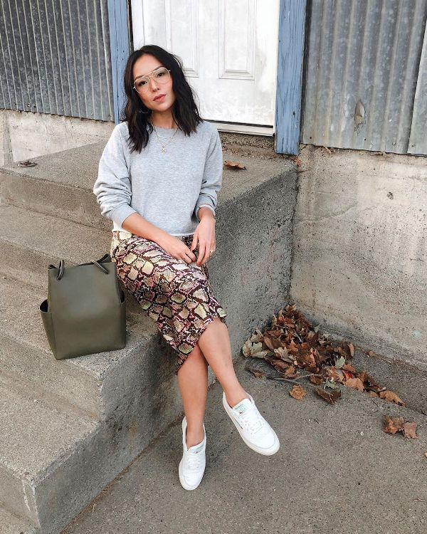 a grey sweatshirt, snakeskin print midi skirt, white sneakers, a green bag and chic and trendy glasses