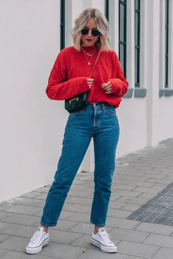 a hot red sweater, blue slim leg jeans, white sneakers, a black bag and layered necklaces