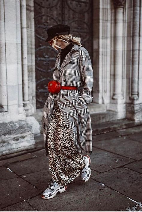 a leopard print maxi skirt, a black turtleneck, a plaid grey trench, grey trainers, a red waist bag and a black cap