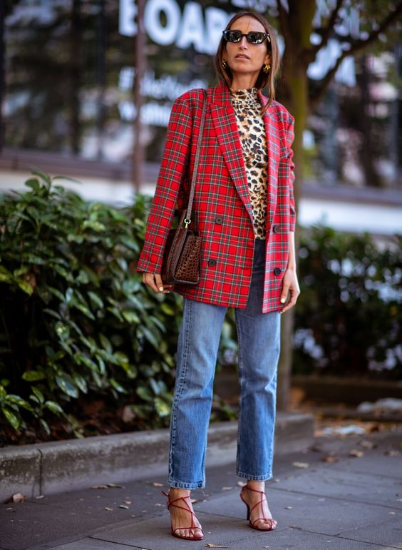 a leopard print turtleneck, a red plaid oversized blazer, blue jeans, red strappy shoes and a reptile print bag