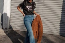 a lovely fall look with a black t-shirt, blue flare jeans, a brown faux fur coat and brown boots is relaxed