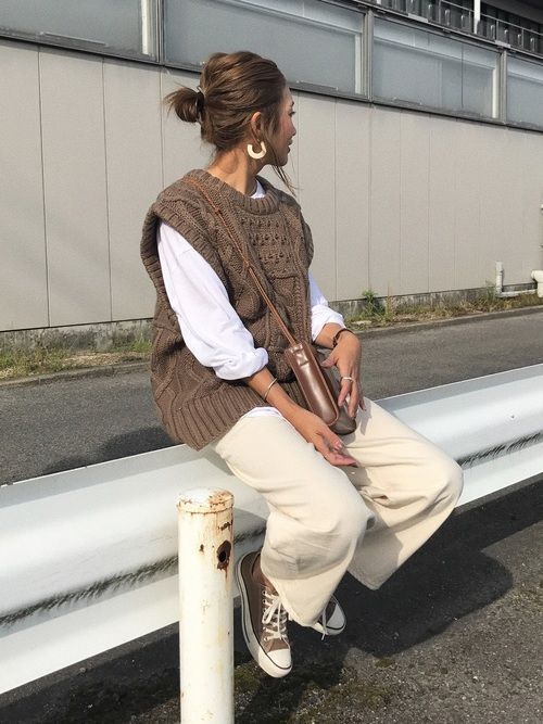 a lovely fall to winter look with a white shirt, a brown patterned vest, white trousers, brown sneakers and a bag