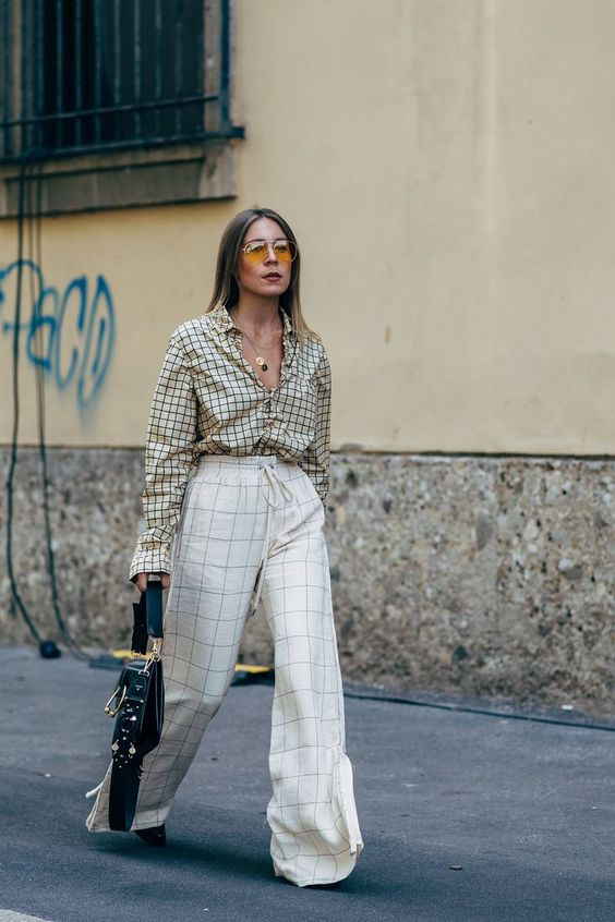 a lovely mix print look in neutrals, with a windowpane print shirt and windowpane wide leg trousers, black shoes and a black bag