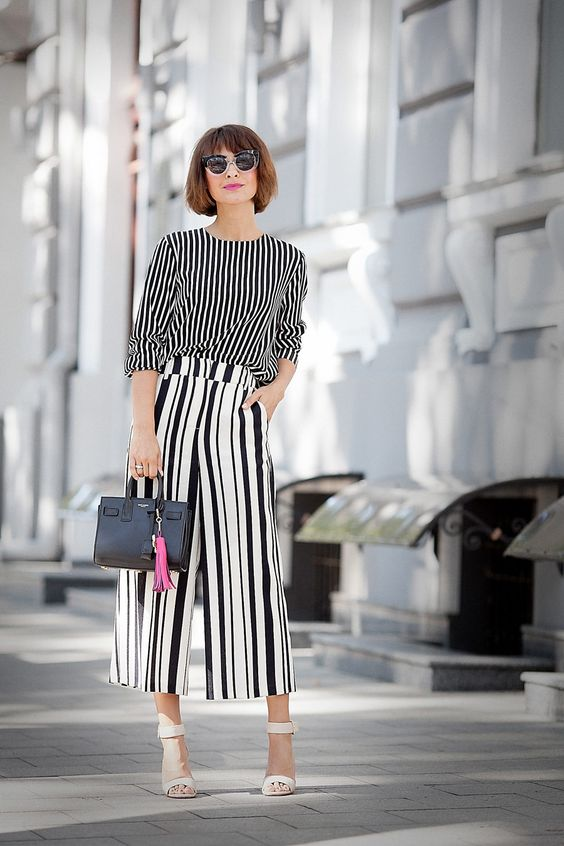 a minochromatic look with a vertical stripe long sleeve top, vertical stripe culottes, white shoes and a small bag