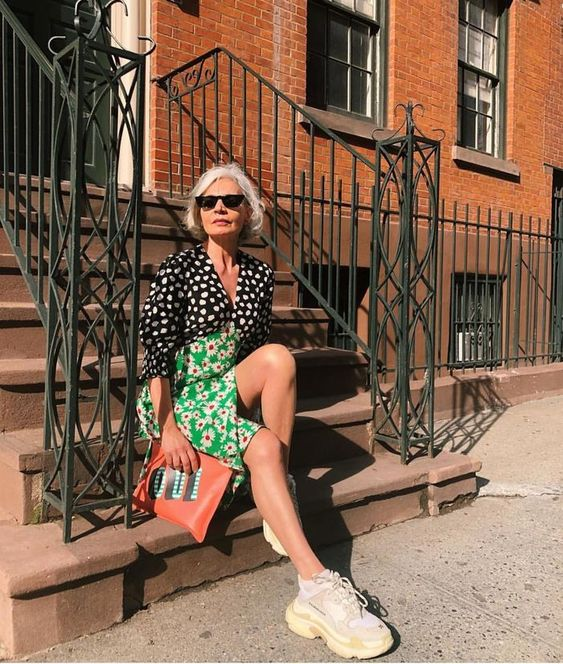 a mix print midi dress showing two different parts - a black and white spot one and a bold green floral one, neutral trainers and a coral clutch
