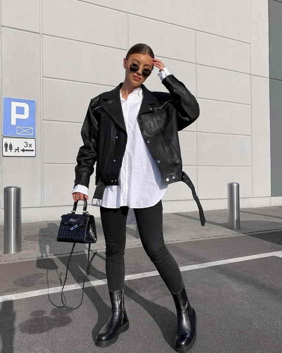 a monochromatic look with an oversized white shirt, black skinnies, black boots, a black leather jacket and a small bag