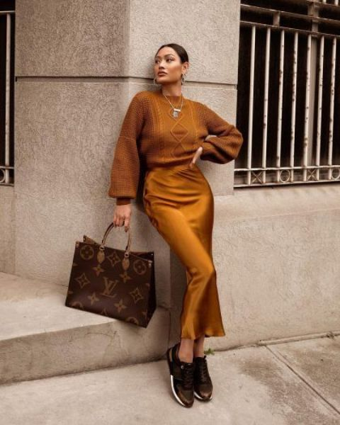 a mustard-colored sweater, a matching slip skirt, black trainers, a brown printed tote and layered necklaces