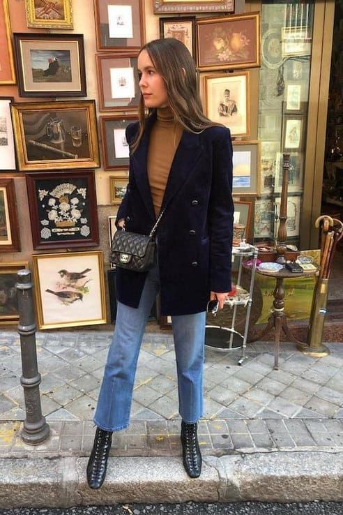 a mustard-colored turtleneck, a navy velvet blazer, blue jeans, black lace up boots and a black bag