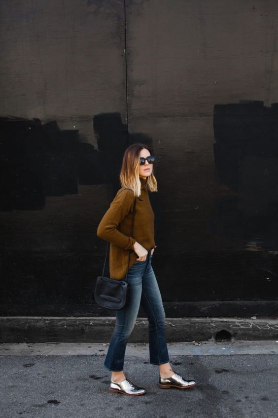 a mustard turtleneck sweater, dark blue cropped flare jeans, silver Oxford shoes and a black bag
