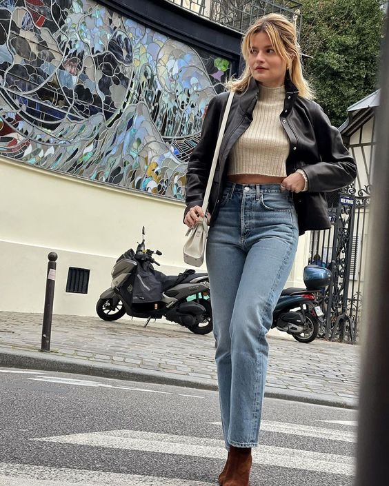 a neutral crop top, blue jeans, a black leather jacket, brown suede boots and a cream crossbody bag