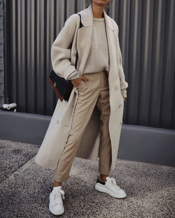 a neutral jumper, tan trousers, a creamy coat, white sneakers and a two tone bag for a bolder accent in the look