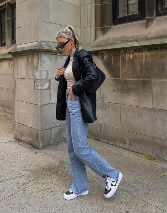 a neutral turtleneck, blue jeans, a black leather blazer and black and white trainers plus a black bag
