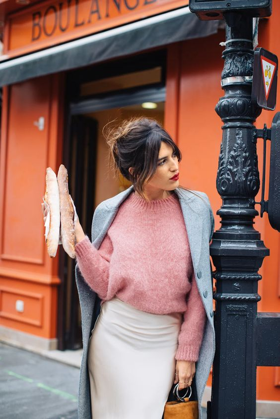a pink sweater, a grey coat, a creamy slip skirt, an amber bucket bag and a red lip for a French chic look