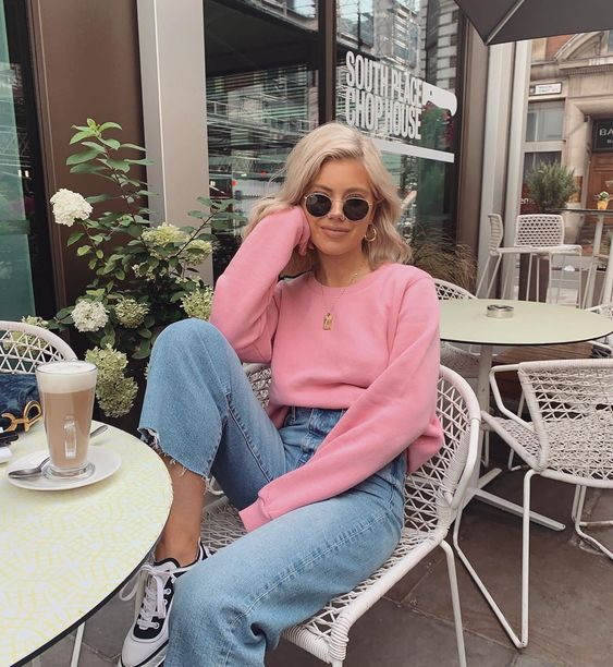 a pink sweatshirt, blue high waisted slim leg jeans, black and white trainers and a cool coin necklace