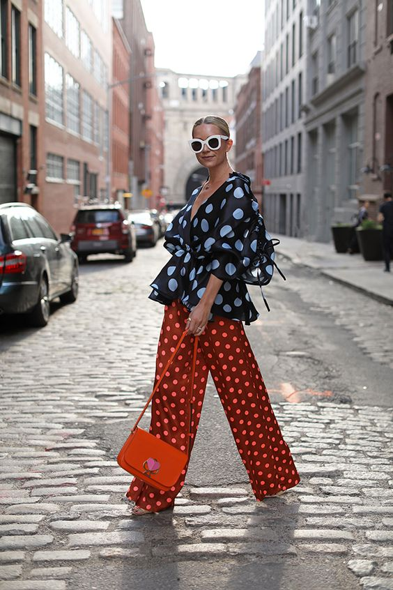 a polka dot outfit with a black top with puff sleeves, rust-colored wide leg trousers, an orange bag for summer