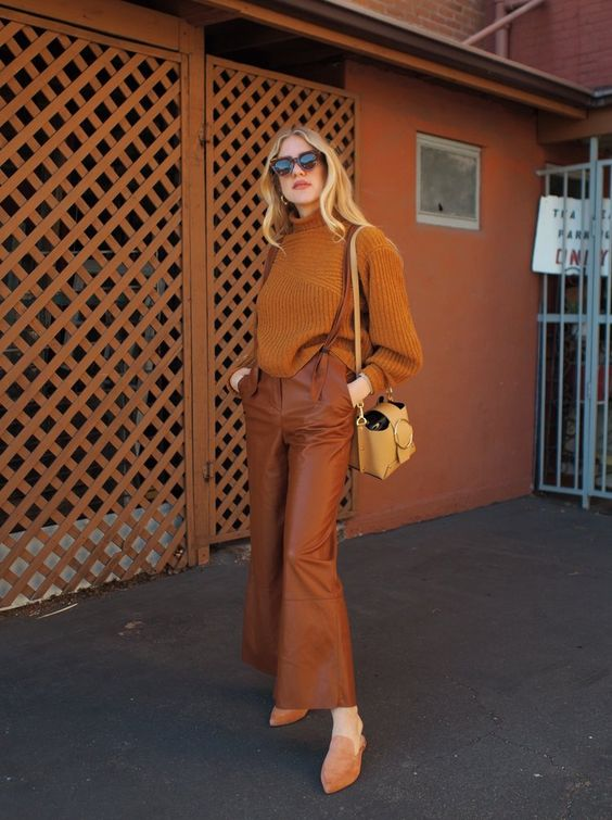 a pretty and comfortable outfit with a rust-colored sweater, leather trousers, mules, a tan bag is a stylish idea