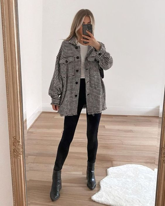 a pretty and comfy look with a white top, black leggings, black booties and a plaid black and white shirt jacket plus a black bag