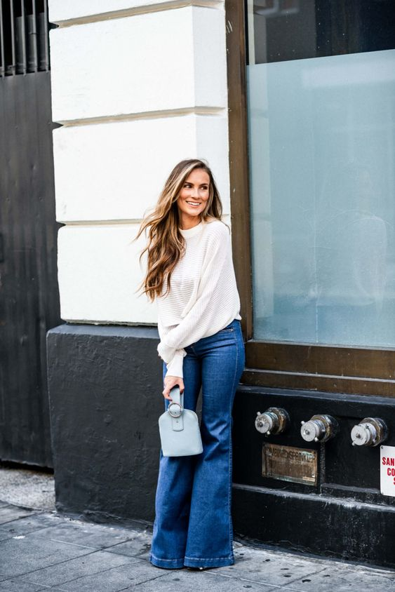 a pretty and easy outfit with a white chunky jumper, navy flare jeans, a light blue mini bag is amazing