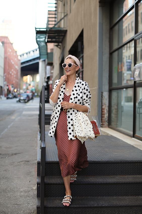 a pretty polka dot girlish look with an oversized blazer, a rust-colored midi dress, a clear bag and embellished shoes