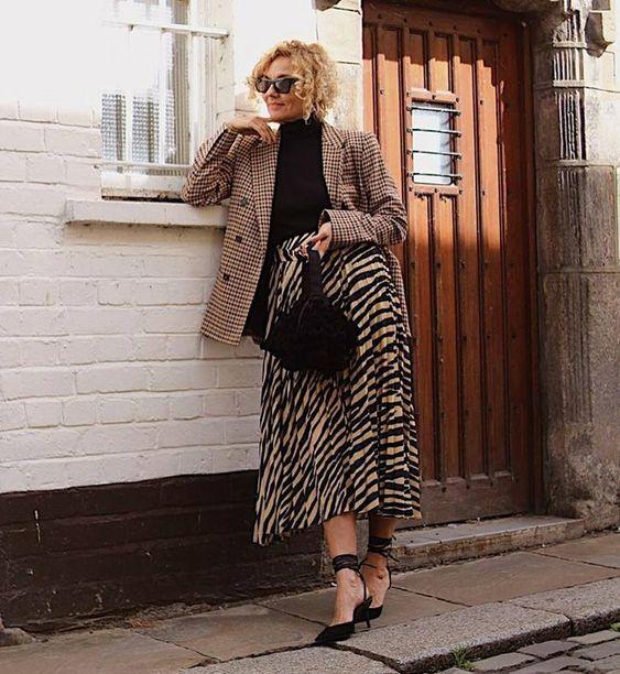 a prety look with a black turtleneck, a plaid oversized blazer, a zebra print midi skirt, black lace up heels and a black bag