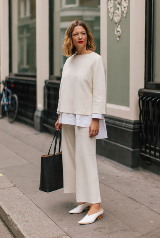 a pure minimalist fall work look with a white oversized shirt, a sweatshirt and trousers, white heels and a black tote