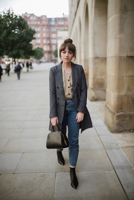 a refined fall look with a tan blouse, blue cropped jeans, a grey coat, black bootis and a black bag