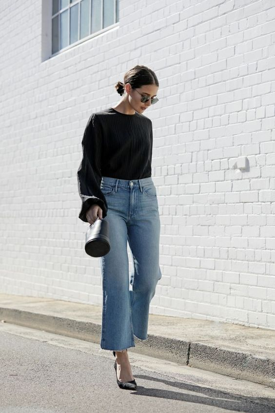 a refined fall outfit with a black bell sleeve blouse, blue jeans, black shoes and a small bucket bag