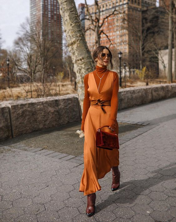 a refined look with a rust-colored turtleneck, an orange slip maxi dress, brown boots, a burgundy bag and a necklace