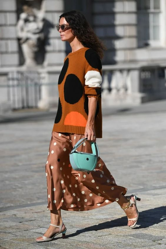 a rust-colored polka dot sweater, a brown polka dot slip skirt, white kitten heels and a blue bag for the fall