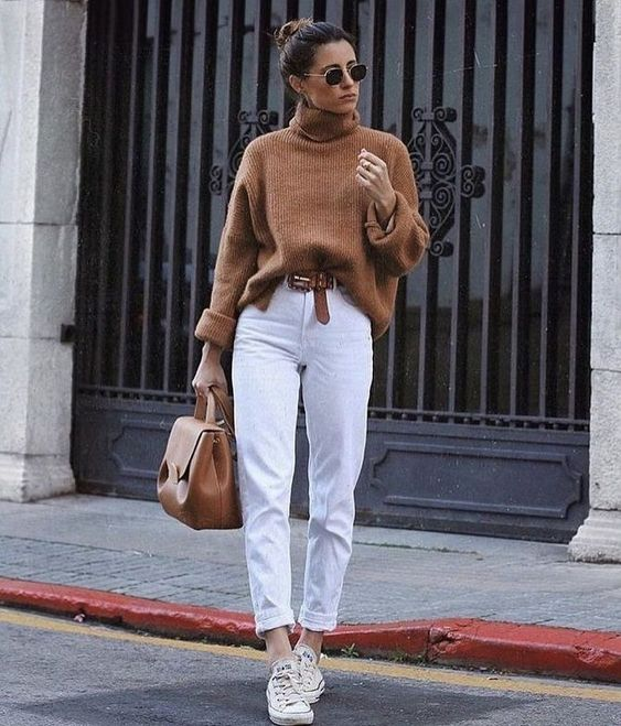 a rust-colored sweater, white slim leg jeans and sneakers, a tan belt and a tan bag for work