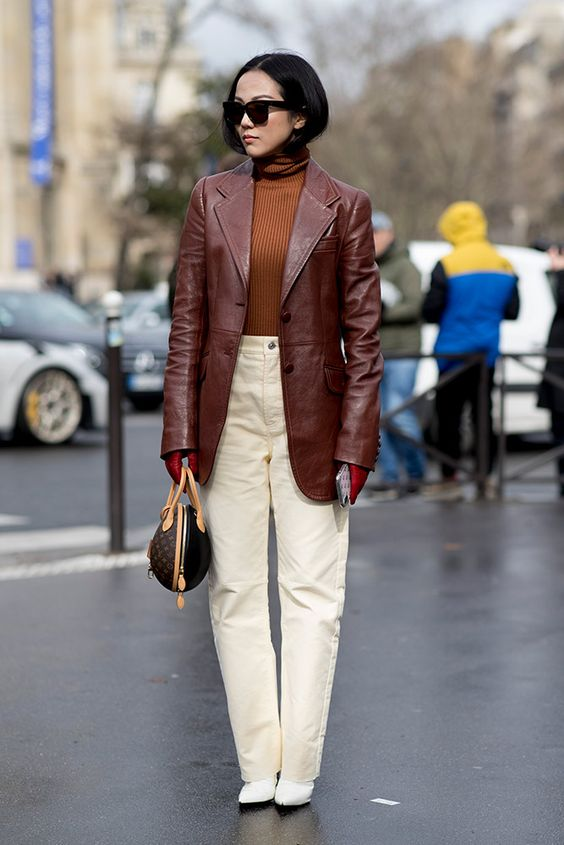 a rust-colored turtleneck, a burgundy leather oversized blazer, white jeans, white booties and a brown bag