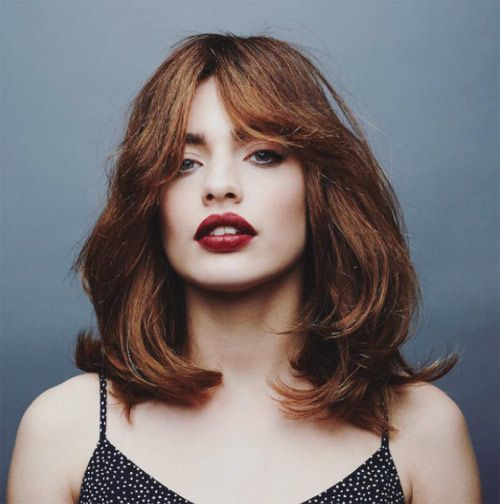 a shaggy layered medium haircut with curtain bangs and a beautiful ginger shade is an amazing solution for the fall