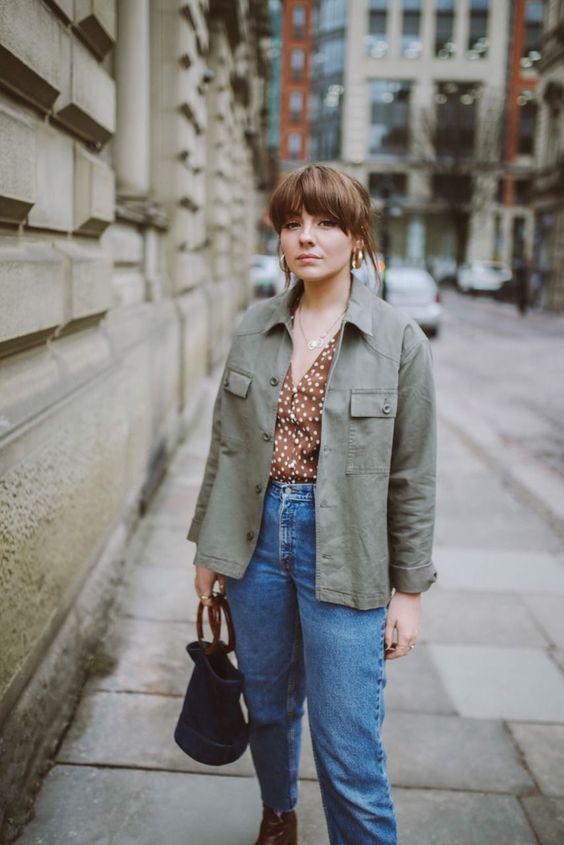 a simple and lovely fall outfit with a rust-colroed polka dot blouse, blue jeans, burgundy boots, a grene utility jacket and a navy bag