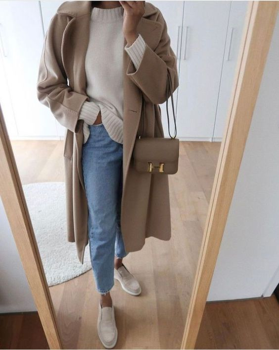 a simple casual fall outfit with a white jumper, blue jeans, tan loafers, a tan coat and a tan crossbody bag