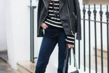 a striped black and white top, a black leather jacket, navy jeans, black boots and a black bag