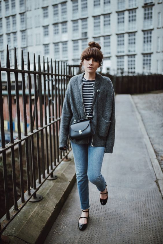a striped long sleeve top, a grey cardigan, blue jeans, black lacquer Mary Jane shoes and a black bag